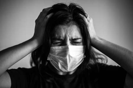 Portrait of a young woman wearing medical sterile mask, having a strong painful headache. Dramatic black and white closeup of a girl being protected from coronavirus. Quarantine stay home concept