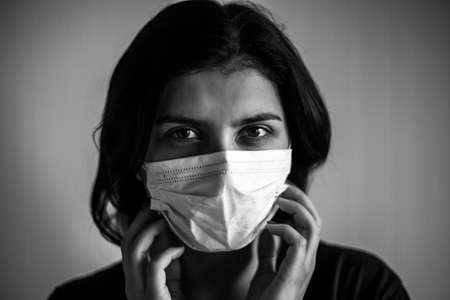 Portrait of a young woman smiling wearing medical mask. Dramatic black and white closeup of a girl being protected from coronavirus and flu illness with sterile mask. Quarantine stay home concept Reklamní fotografie