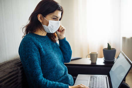 Businesswoman stays home and works during coronavirus epidemia quarantine. Female worker touches her medical mask and typing on a laptop. Covid-19 pandemia spread prevention concept Reklamní fotografie