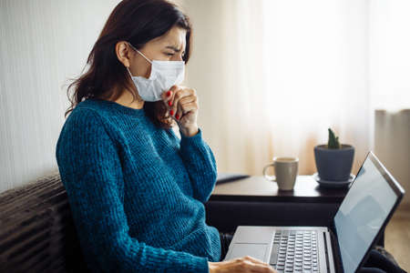 Businesswoman stays home and works during coronavirus epidemia quarantine. Female worker wearing a medical mask, coughs and typing on a laptop. Covid-19 pandemia spread prevention concept