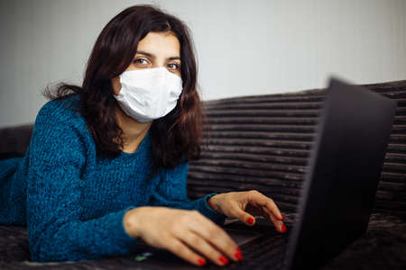 Young businesswoman working from home during quarantine due to coronavirus pandemia. Beautiful girl stays home wearing medical mask and typing on a laptop. Covid-19 epidemia worldwide concept