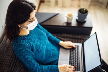 Businesswoman stays home and works during coronavirus epidemia quarantine. Female worker wearing a medical mask and typing on a laptop. Covid-19 pandemia spread prevention concept