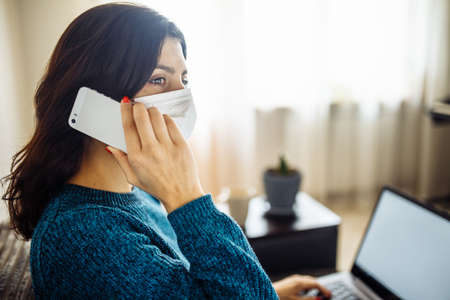 Businesswoman stays home and works during coronavirus epidemia quarantine. Female worker wearing a medical mask and typing on a laptop, talks via cellphone. Covid-19 pandemia spread prevention