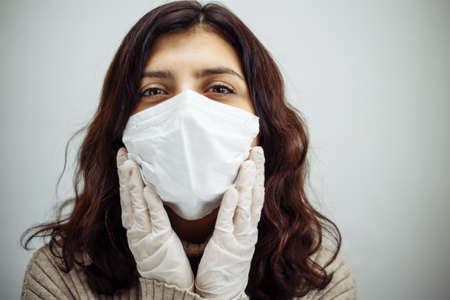 Portrait of a young woman holds hands on her head and has to stay home during quarantine due to coronavirus pandemia. Beautiful girl wearing medical mask and gloves. Covid-19 epidemia concept