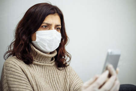 Young woman taking selfie photogragh and working from home during quarantine due to coronavirus pandemia. Beautiful girl stays home wearing medical mask and gloves. Covid-19 epidemia concept