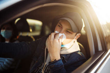 A man sneeze while driving a car during coronavirus quarantine. A taxi driver feels sick and threaten the passager's health. Safe driving problem to stop spread of the virus