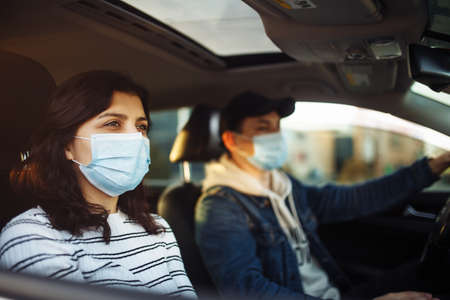 A girl and a boy driving in a car during coronavirus quarantine wearing medical masks. Safe taxi and healthcare during pandemic covid-19. Passangers virus safety concept Reklamní fotografie