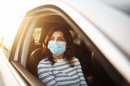 A woman wearing a medical sterile mask in a taxi car on a backseat looking sideway out of open window. Girl passenger waiting in a traffic jam during coronavirus quarantine. Healthcare safety concept