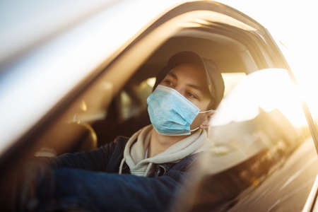 A boy drives a car in a medical sterile mask during coronavirus pandemic quarantine. Man waiting stuck in a traffic jam looking for prospects. Stop spread of virus by self protection
