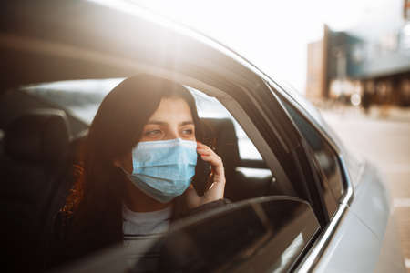 Woman wearing a medical sterile mask in a taxi car on a backseat looking out of window talking on the phone. Girl passenger waiting in a traffic jam during coronavirus quarantine. Healthcare concept