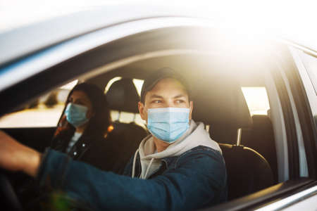 Man driving a car wearing sterile medical mask. Taxi driver with a passanger stuck in a traffic jam during coronavirus quarantine isolation in the city. Prevernt spread of covid-19 concept
