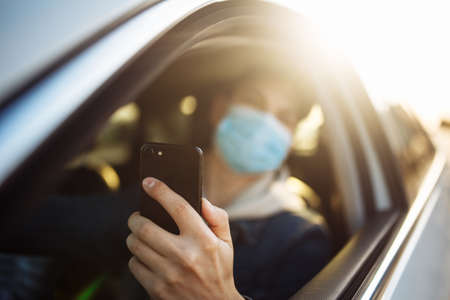 A man wearing a medical mask holds a mobile cell phone in his hand while driving a car. Boy driver checking coronavirus world news in a traffic jam. Isolation and healthcare during quarantine concept