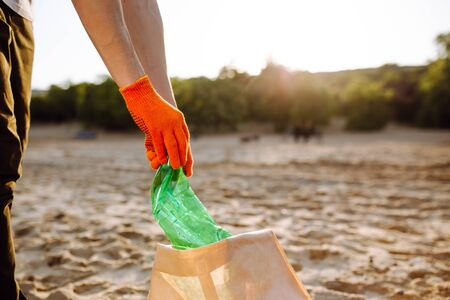 Young male volunteer picks up plastic garbage on the ocean coast. A man collects waste on the seaside to save ecology and protect environment. Recycle litter and pollution concept Stock Photo