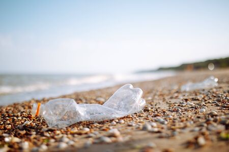 An empty plastic bottle thrown out on the ocean beach coast. Garbage and sea pollution, global disaster because of non recycled waste. Environmental problem and ecology concept