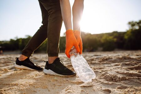 Young male volunteer picks up plastic garbage on the ocean coast. A man collects waste on the seaside to save ecology and protect environment. Recycle litter and pollution concept
