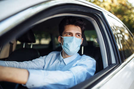 Young man sits behind the steering wheel in the car wearing sterile medical mask. Boy taxi driver works hard during coronavirus outbreak. Social distance, virus spread prevention and treat concept
