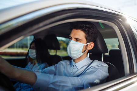 Young man taxi driver wears sterile medical mask in the car. A boy behind the car steering wheel safely driving for business matter keeping social distance. Coronavirus pandemic concept