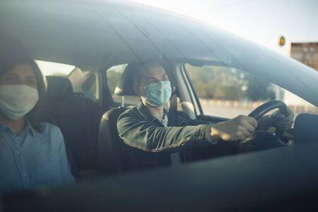 Taxi driver wearing sterile medical mask hold his hands on the steering wheel. Young man drives a car with a passenger during coronavirus epidemic. Social distance, pandemic, health concept.