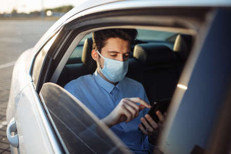 Young businessman takes a taxi and looks into his cell phone wearing sterile medical mask. A man sits on the back seat of taxi and takes a ride during coronavirus pandemic. Social distance concept Stock Photo