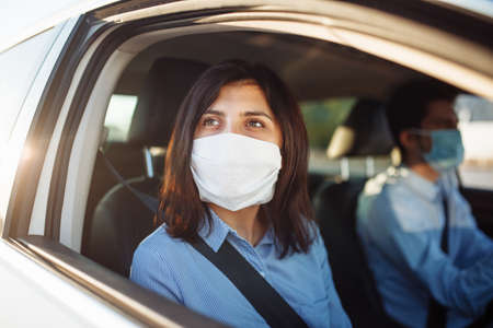 Young girl passenger takes a ride by taxi during the coronavirus pandemic quarantine. Woman looks out of the car window wearing sterile medical mask. Social distance and health safety concept Imagens