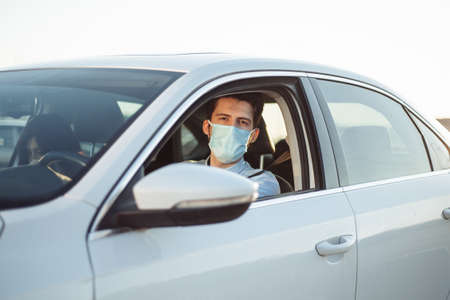 Young boy taxi driver gives passenger a ride wearing sterile medical mask. A man in the car behind the steering wheel works during coronavirus pandemic. Social distance and health safety concept Stock Photo
