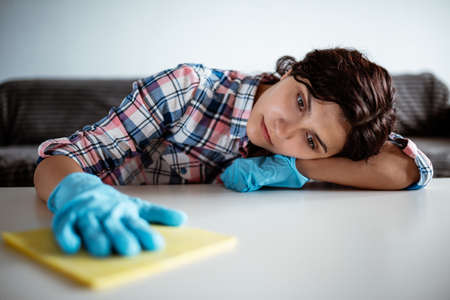 Young woman getting bored while making home cleaning with a microfiber rag wearing blue rubber gloves. Healthcare during coronavirus and disinfection concept