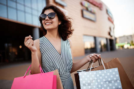 Young beautiful woman shopaholic walks out the shopping center with a pack of bags with purchases. Pink shopper in the hand of an obssessed girl. Shopping, clothes and spending money concept Reklamní fotografie
