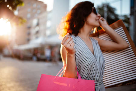 Happy girl stands near boutique shop holding a few bags with purchases. Young woman is glad to buy new clothes during sales season for a reasonable price. Shopping, discount, spend money concept Фото со стока