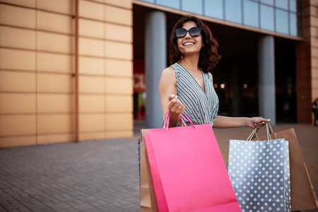 Happy girl stands near boutique shop holding a few bags with purchases. Young woman is glad to buy new clothes during sales season for a reasonable price. Shopping, discount, spend money concept Reklamní fotografie