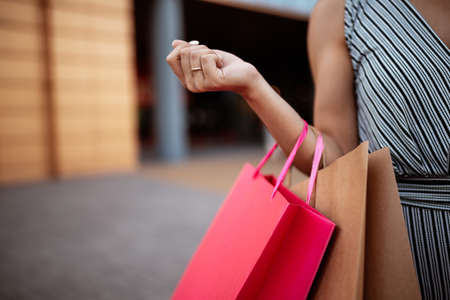 Closeup of young attractive woman holding a few shopping bags with newly purchased goods and clothes. Girl holds colourful packs full of bought things in her hands. Shopping and spendings concept.