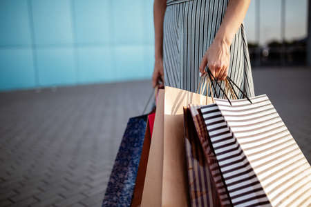 Closeup of young attractive woman holding a few shopping bags with newly purchased goods and clothes. Girl holds colourful packs full of bought things in her hands. Shopping and spendings concept