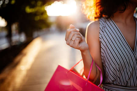 Happy girl stands near boutique shop holding a few bags with purchases. Young woman is glad to buy new clothes during sales season for a reasonable price. Shopping, discount, spend money concept Stok Fotoğraf