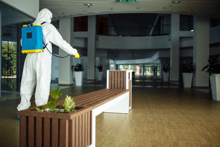 A man wearing protective suit is disinfecting a bench in an empty shopping mall with sanitizing spray. Cleaning up the public place to prevent covid spread. Healthcare precautions and safety concept. Reklamní fotografie - 152019723