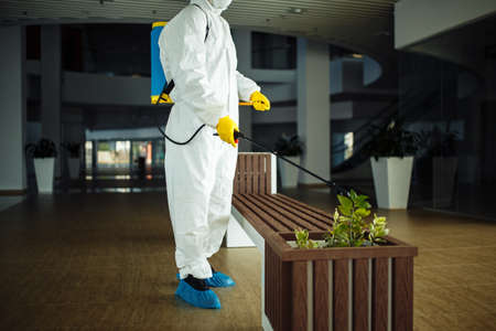 A man wearing protective suit is disinfecting a bench in an empty shopping mall with sanitizing spray. Cleaning up the public place to prevent covid spread. Healthcare precautions and safety concept. Reklamní fotografie - 152019726
