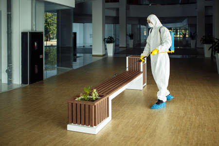 A man wearing protective suit is disinfecting a bench in an empty shopping mall with sanitizing spray. Cleaning up the public place to prevent covid spread. Healthcare precautions and safety concept. Reklamní fotografie