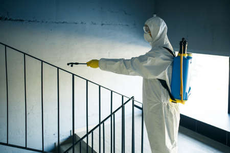 Sanitizing worker cleaning up the staircase at the shopping mall with an antiseptic to prevent covid-19 spread. A man in a disinfection suit sprays stairs. Healthcare, quarantine and hygiene concept.