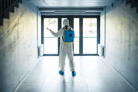 A man wearing protective disinfection suit and a spray stands in front of a glass doors under the staircases. Worker cleaning up the business center. Healthcare, covid-19 concept. Reklamní fotografie - 152019761