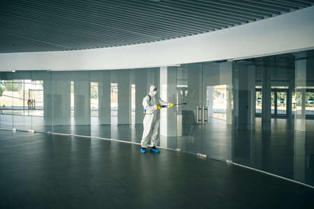 A man wearing disinfection suit spraying with sanitizer the glass doors handles in an empty shopping mall to prevent covid-19 spread. Health awareness, clean, defence concept.