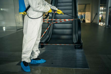 Sanitizing worker disinfects the escalator with a spray at the empty shopping mall to prevent the covid-19 spread in public places. Healthcare, clean, isolation and quarantine concept.
