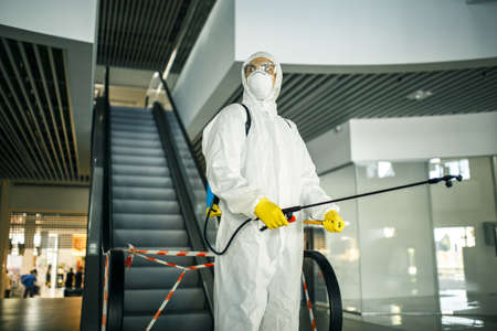 Portrait of a man in a sanitizing disifection suit holding spray near the escalator in an empty shopping mall. A volunteer cleaning up the public places to prevent covid-19. Health awareness concept. Reklamní fotografie - 152019792