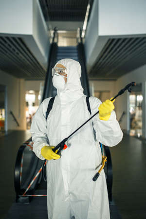 Portrait of a man in a sanitizing disifection suit holding spray near the escalator in an empty shopping mall. A volunteer cleaning up the public places to prevent covid-19. Health awareness concept
