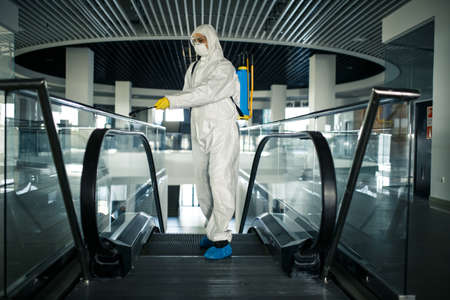 Disinfection worker wearing a protective suit professionally cleans up an escalator in an empty business center. A man equiped with antibacterial clothes sterilizes shopping mall. Covid concept.