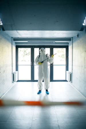 A man wearing protective disinfection suit and a spray stands in front of a glass doors under the staircases. Worker cleaning up the business center. Healthcare, covid-19 concept. Reklamní fotografie