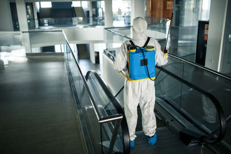 Disinfection worker wearing a protective suit professionally cleans up an escalator in an empty business center. A man equiped with antibacterial clothes sterilizes shopping mall. Covid concept. Reklamní fotografie - 151922468