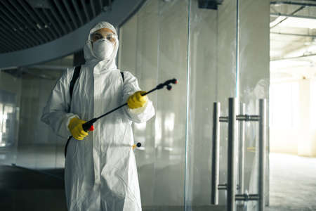 Sanitary worker sprays an empty business center with antiseptical liquid to prevent covid-19 spread. A man wearing disinfection suit cleaning up the shopping mall. Nobody, health, isolated concept. Reklamní fotografie - 151922470