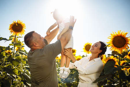 Happy family having fun in the field of sunflowers. Father and mother throw their daughter in the air and smile. Girl likes playing with her parents. Summer season, freedom, family value concept.