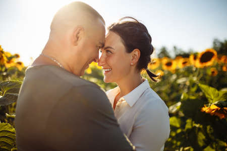 Young couple having fun during the summer day on the sunflower field. Man and woman hug and kiss and being happy showing love. Freedom, joy, unity and family values concept. Reklamní fotografie - 153302789