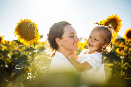 Happy mother with the daughter in the field with sunflowers having fun on a sunny summer day. Family value, unity, happiness, love and joy concept.