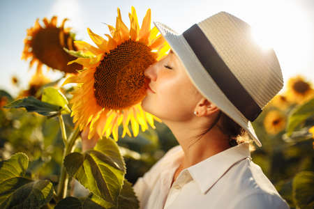 Beautiful young woman in a white dress enjoying nature. Happy smiling female standing in sunflowers field and smell a flower. Amazing sunset. Warm photo. Freedom and joy concept.