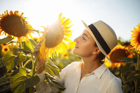 Beautiful young woman in a white dress enjoying nature. Happy smiling female standing in sunflowers field and smell a flower. Amazing sunset. Warm photo. Freedom and joy concept. Reklamní fotografie - 153279089